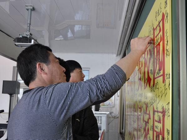 """参加活动人员还在""""建设平安校园 共建美好家园""""的展板上进行签字."""