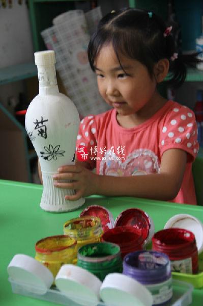 6月5日,博兴县实验小学附属幼儿园,小朋友正在废弃的酒瓶上绘画,将废
