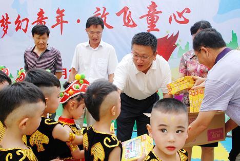 包旭(后左三)为幼儿园的小朋友送去节日的礼物