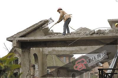 昨天,江北区开展违法建筑集中整治行动,执法人员对太阳海岸别墅区违法建筑进行强拆。 昨日,这个依附在别墅身上的违法建筑被相关部门依法实施强拆。江北区违法建筑整治工作指挥部办公室(下简称江北整违办)人士介绍,这个别墅小区有30户违建,已被拆除的有13处。 别墅悄然长出了背包 太阳海岸位于江北铁山坪街道,共有832套别墅和洋房,面积近33万平方米。其中,别墅有500多套,从2009年开始分期交房。 近段时间,有不少别墅业主开始装修。可是有的业主装修时,却远远超过了正常范围,打起了歪主意:主要就是多搭多建
