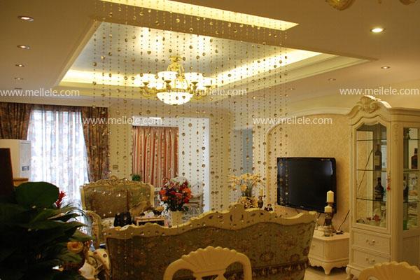 这是一个欧式风格的客厅珠帘隔断,也是客厅与餐厅的隔断,其实想要珠帘隔断的风格与家居风格相搭配特别简单,这张客厅珠帘隔断效果图的欧式风格是以黄色为主色调,我们只需要使用全透明的珠帘安装上就可以了,在顶部设计一盏黄色的灯,灯光照耀下来,整个珠帘就能够很好的与整个空间融为一体了。